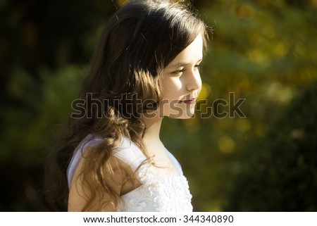 Closeup portrait of beautiful small caucasian girl with long loose dark curly hair black eyelashes and rosy lips in white dress on green blurry background, horizontal photo - stock photo