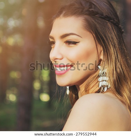 Closeup portrait of beautiful smiling bohemian young woman with silver butterfly boho earrings with balayage dyed hair and braid outdoors in park in summer. Square format, retouched. - stock photo