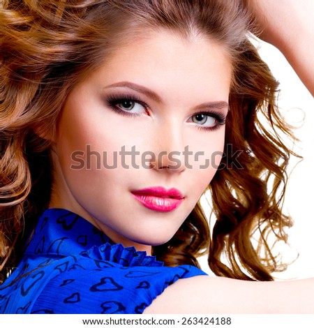 Closeup portrait of beautiful smiling woman in blue dress looking at camera posing at studio on a white background. - stock photo