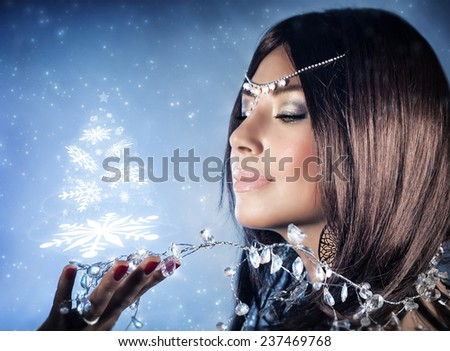 Closeup portrait of beautiful snow queen with crown on head holding on hand magical glowing Christmas tree, winter fashion and makeup - stock photo