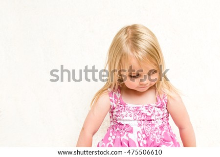 Closeup Portrait of Beautiful Toddler Girl Looking Down on Neutral Background