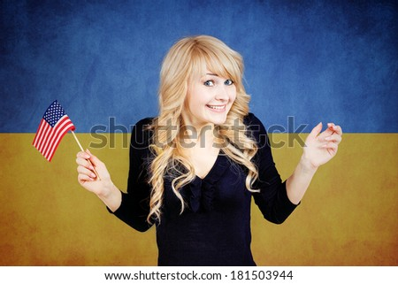 Closeup portrait of beautiful Ukrainian blonde smiling woman holding USA flag in one hand, isolated on Ukraine national flag background. Politics, revolution, Russia conflict protection, negotiation - stock photo