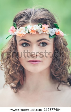 Closeup portrait of beautiful white Caucasian girl with hazel eyes, long wavy curly hair and flowers chaplet on head. Attractive young woman model in park outside, country village hippie style - stock photo