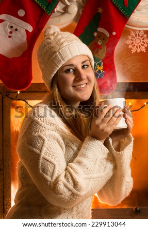Closeup portrait of beautiful woman in woolen sweater drinking tea at fireplace - stock photo