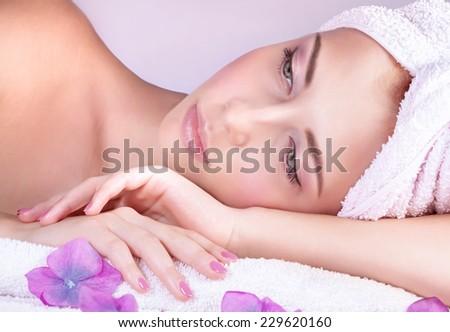 Closeup portrait of beautiful woman lying down on massage table, enjoying aromatherapy in luxury spa salon, healthy lifestyle concept - stock photo