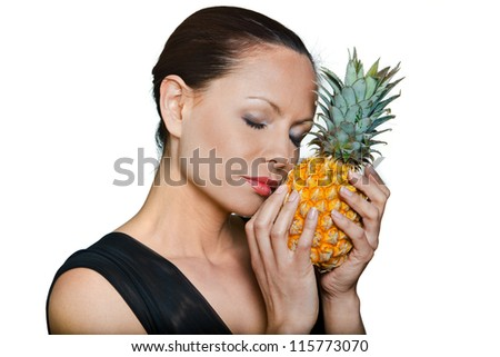 Closeup portrait of beautiful woman smelling fresh pineapple with eyes closed in studio isolated on white background - stock photo