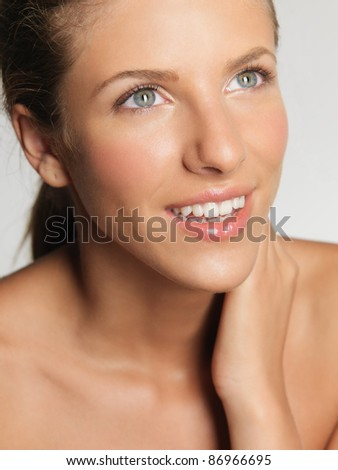 closeup portrait of beautiful woman touching her face, looking into the light - stock photo