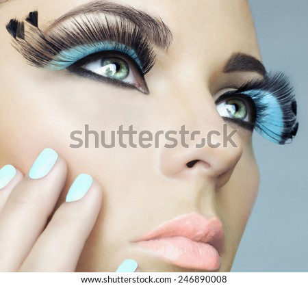 Closeup portrait of beautiful woman with color eyelashes. Makeup and manicure - stock photo