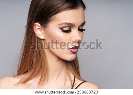 Closeup portrait of beautiful woman with makeup looking to the side, closed eyes
