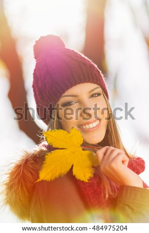 Closeup portrait of beautiful young blonde Caucasian woman in park in autumn holding a yellow leaf, smiling. Back light, natural light, medium retouch, vibrant color, natural light leak.