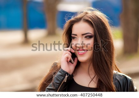 Closeup portrait of beautiful young blonde talking to mobile phone - stock photo