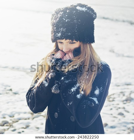 Closeup portrait of beautiful young blonde teenage girl in black coat and artificial fur hat posing. Cute young woman in snow in winter. Filter, instagram look, square format image. - stock photo