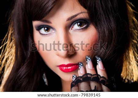 Closeup portrait of beautiful young brunette girl with long dark ringlets and fine art lacy manicure on black background - stock photo