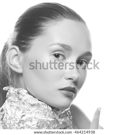 Closeup portrait of beautiful young brunette woman with silver  foil on neck. Creative makeup. Isolated over white background. Black and white