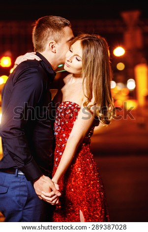 Closeup portrait of beautiful young couple kissing at night city street at colorful lights background.