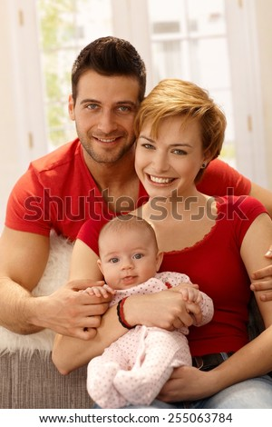 Closeup portrait of beautiful young family with newborn baby girl, smiling, looking at camera. - stock photo