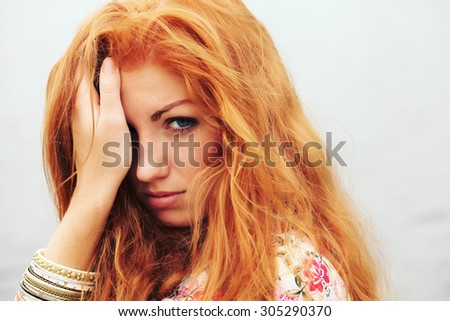 Closeup portrait of beautiful young fashion model with long red haired wavy hair posing wearing bracelet standing at the river on sunny summer day. Artsy bohemian style. Fashion lifestyle, outdoors.  - stock photo