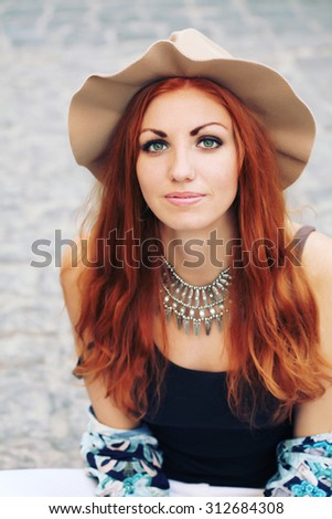 Closeup portrait of beautiful young fashion model with long wavy hair posing outdoors, wearing beige hat and necklace. Happy carefree lifestyle. Bohemian outfit. Street style.  - stock photo