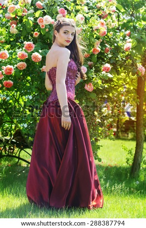 Closeup portrait of beautiful young fashion woman with red lipstick is sitting in roses garden - stock photo