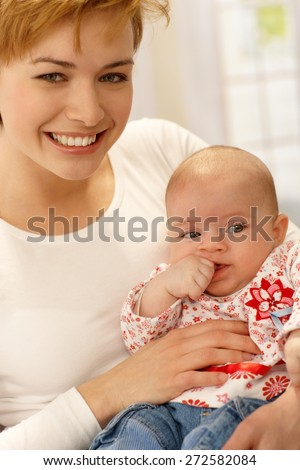 Closeup portrait of beautiful young mother holding baby girl, smiling happy. - stock photo