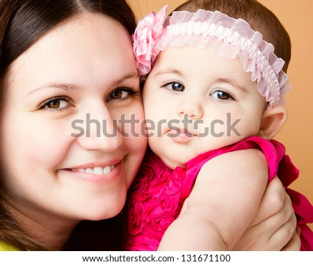 Closeup portrait of beautiful young mother with cute daughter - stock photo