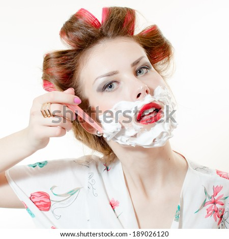 closeup portrait of beautiful young pinup woman attractive girl shaving face and looking at camera isolated on white background - stock photo