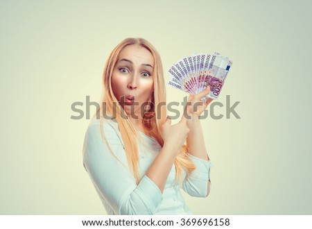 Closeup portrait of beautiful young smiling woman with euro money bills showing pointing money thumb up isolated green background with copy space. Sale, saving banking concept. Positive human emotions - stock photo