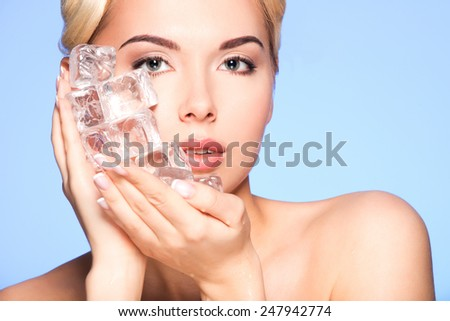 Closeup portrait of beautiful young woman applies the ice to face on a blue background.