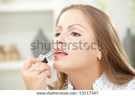 Closeup portrait of beautiful young woman applying lipstick.