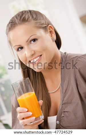 Closeup portrait of beautiful young woman drinking orange juice.