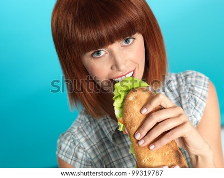 closeup portrait of beautiful young woman, eating a big sandwich, smiling, on blue background
