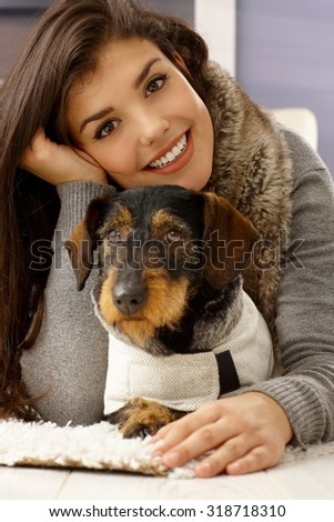 Closeup portrait of beautiful young woman hugging dog, smiling happy, looking at camera. - stock photo
