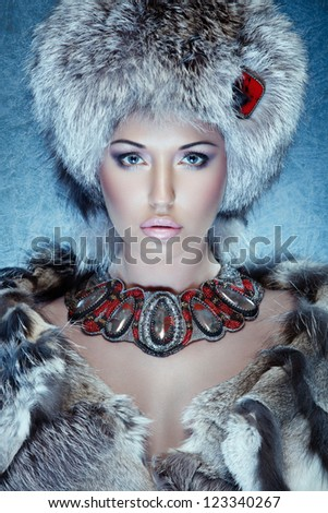 closeup portrait of beautiful young woman in fur clothes with necklace against blue ice
