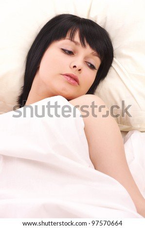 Closeup portrait of beautiful young woman lying in bed - stock photo