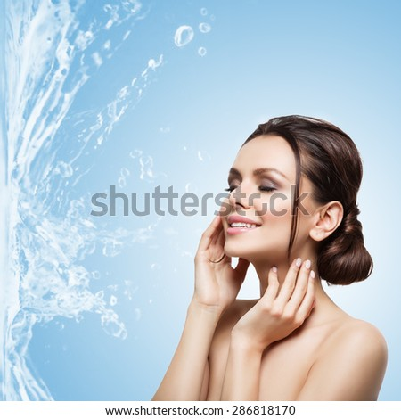 Closeup portrait of beautiful young woman over blue background with water splash. Isolated. Copy space. Square composition. - stock photo