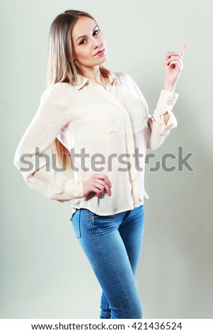 Closeup portrait of beautiful young woman pointing her finger towards blank space - stock photo