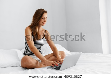 Closeup Portrait Of Beautiful Young Woman Using Laptop Computer, Sitting On Bed. Female Working Online, Typing On Notebook Keyboard At Home.