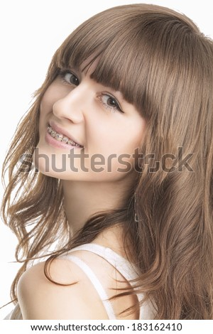 Closeup Portrait of Beautiful Young Woman With Brackets on Teeth. Isolated Over White Background. Vertical Image - stock photo