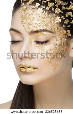 Closeup portrait of beautiful young woman with golden foil on face and lips. Creative makeup. Long hair. Isolated over white background. - stock photo