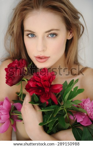 Closeup portrait of beautiful young woman with perfect skin. Pretty caucasian model holding peonies. - stock photo