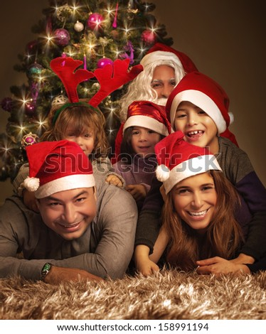 Closeup portrait of big happy family with Santa Claus lying down near Christmas tree, holiday celebration, joy and happiness concept - stock photo
