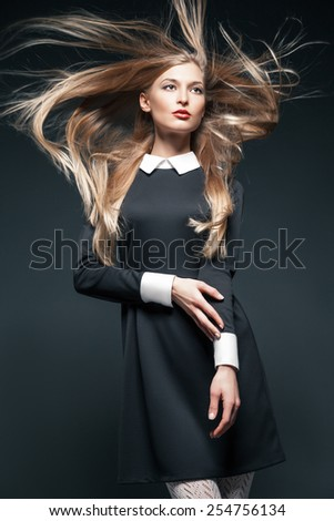 Closeup portrait of blond fashion model posing with hair fluttering in the wind - stock photo