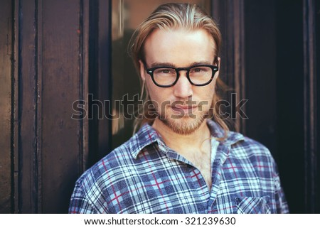 closeup portrait of blond man with long hair and glasses. Thoughtful man - stock photo