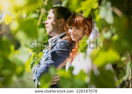 Closeup portrait of bride hugging groom from back at park - stock photo