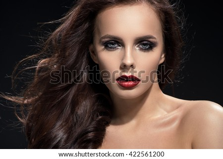 Closeup portrait of brunette woman on black background