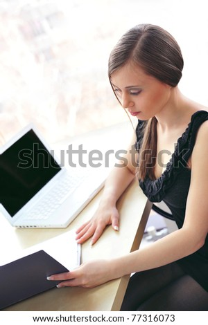 Closeup portrait of business woman working with folder of documents and laptop against wide french window - stock photo