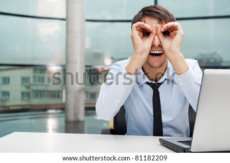 Closeup portrait of businessman looking for employees. Sitting indoors at his office in front of laptop and looking to camera with binoculars from arms - stock photo