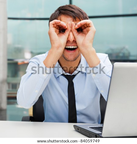 Closeup portrait of businessman looking for employees. Sitting indoors at his office in front of laptop and looking to camera with binoculars from arms