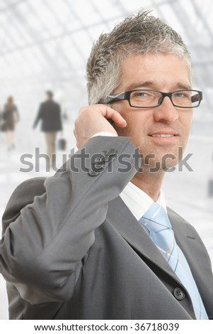Closeup portrait of businessman talking on mobile in office lobby.
