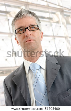 Closeup portrait of businessman wearing grey suit and glasses, in front of office building windows.